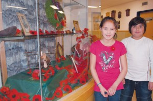 From left, Kendall Collins and Max Bloomstrand stand beside a special Remembrance Day display at Princess Alexandra School.