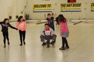 Hailey Raiwong-Delorey and Hailey Pike cheer on Allen Gostick on a tiny bike, along with cheers from Carson Borchuk and Gabi Morse. The youth took part in a  fun race at the Hay River curling club youth windup on March 18. Angele Cano/NNSL photo