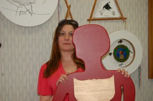 K'atlodeeche First Nation Victim Services Program supervisor Jaimie Forsey stands with a wooden cut-out as part of the Silent Witness Project. The cut-out represents a woman who has died at the hands of her partner. The project will be launched locally at an April 24 & 25 workshop as part of National Victims of Crime Awareness Week. Angele Cano/NNSL photo
