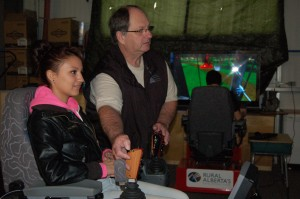 Angele Cano/NNSL photo Michelle Buckley, left, gets help on the controllers from instructor Bevan Davidson on a harvester processor simulator as part of a new forestry course at DJSS.