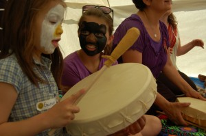 Sarah Ladik/NNSL photo Emerson Beck, left, gets some instruction from Madison Beck on how to follow the beat with the drum at Aboriginal Day festivities hosted by the Hay River Metis Council.