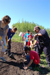 Sarah Ladik/NNSL photo From left, Jessica Gilbert, Jessica Jean, Conner McKay-Ivanko, Shayla Moore, Tyson Maher, Allen Gostick and Const. Steve Beck plant potatoes for the Hay River Soup Kitchen at the Hay River Community Gardens.