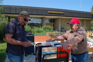 Tim Gayton, left, and James Danish sift through the books available at the used book sale in front of the NWT Centennial Library, June 28. The library's advocates say it provides a much-needed service to the community. -- Sarah Ladik/NNSL photo