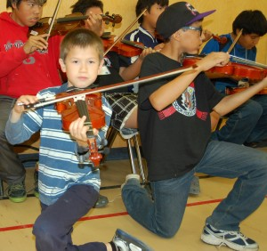 Sarah Ladik/NNSL photo Seven-year-old Ethan Hayne, left, and Lucas Kotchilea, 10, get warmed up for orchestra class with their teacher Wesley Hardisty on July 5.