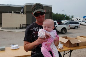 Sarah Ladik/NNSL photo Jodi Seaton holds his daughter, five-month-old Piper Seaton, at the Formula for Life bake sale on July 5. Despite now having the food she needs, Piper still weighs only 11 pounds.