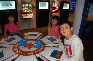 Sarah Ladik/NNSL photo From left, Layla Campbell, Meghan Campbell and Braden Lamb try out the interactive features in the 'It's an Honour' travelling exhibit when it stopped for one day only in Hay River on Aug. 22.
