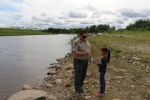 Sarah Ladik/NNSL photo Department of Environment and Natural Resources officer Albert Bourque helps Angelia Nitsiza ready her fishing rod for a cast at a culture camp activity on the West Channel on Aug. 22.