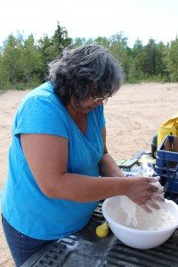 photo courtesy of Cara Orr Sharon Pekok, the executive director at the Soaring Eagle Friendship Centre, makes the batter for bannock-on-a-stick at Sandy Creek for the second-to-last day of a summer culture camp on Aug. 29.