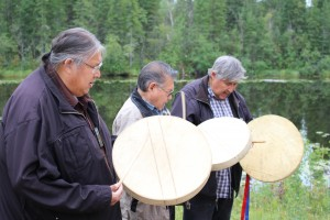 Sarah Ladik/NNSL photo From left, K'atlodeeche First Nation Chief Roy Fabian, Philip Fabian and Frank Fabian drum and sing at a fire-feeding ceremony on Aug. 30 to bless the area on which the community's new wilderness lodge is being built.