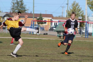 Sarah Ladik/NNSL photo Diamond Jenness Secondary School's Tyrell Wilgosh makes a daring play against Fort Smith's Mitchell Porter in a game on Sept. 21 during the Elks' Outdoor Soccer Tournament.