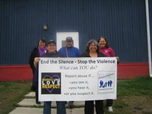 photo courtesy of Eileen Teng From left, Noella Cayen, Rhonda Plamondon, Kim Beaulieu, Sharon Pekok and Dora Unka prepare to march on Oct. 1 for Family Violence Awareness Week, behind a sign asking people to speak out if they suspect violence.