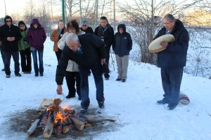 Sarah Ladik/NNSL photo Foreground, from left, Clara Sabourin and Cheeto Lamalice place the offerings of food and tobacco into the fire while K'atlodeeche First Nation Chief Roy Fabian sings a prayer song to open the NWT Tourism conference and AGM in Hay River Nov. 5.