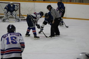 Defenseman Bryden Patenaude (foreground, left) waits for a pass from the faceoff between Patrick Smith and a player from High Level at a game officiated by Tim Borchuck Nov. 16. Photo by Sarah Ladik NNSL