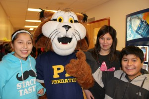 From left, Sierra Balsillie, Princess Alexandra School mascot Whiskers, Roxie Beaulieu and Max Bloomstrand, celebrate after a cheque presentation from Diavik Diamond Mines on Dec. 4.