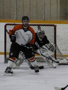 Kyle Kugler, left, of Yellowknife and Lance Lennie, a goalie with Hay River, compete on Feb. 9 in a Northern Hockey Challenge game in Hay River. -- NNSL file photo