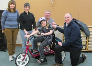 From left, Bev Tybring, Andrea Pittman, Keith Linehan, and Steve Anderson help Natalie Linehan (centre) learn how to ride her new bike. Natalie's disability means she can't ride a regular bike without help and her new tricycle will allow her more independence. Photo courtesy of Sandy Couger