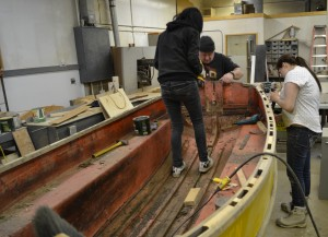 Kristen Martel, left, Marc Schmitz, and Brooklyn Cayen work on a Davidson dinghy in the NTCL carpentry shop as part of the NT Boats Project refurbishment efforts March 5. Photo courtesy of Alice Coates