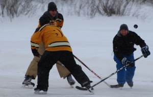 From left, Cory Strange (back to camera), Bradley Harrison, and John Wallington play in a game March 8 at Polar Pond Hockey. Photo by Sarah Ladik NNSL