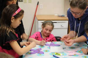 Penelope Berrub, left, Helene McKay-Ivanko, and Anna Bergen make butterflies at a the craft portion of the Start Your Month Off Right activities at the Centennial Library April 5.
