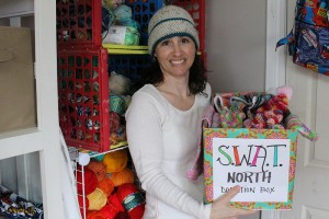 Jessica Latour shows off one of the many hats she made and a box full of donations for SWAT North at her home May 8. Photo by Sarah Ladik NNSL