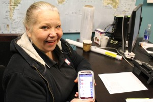 Super A employee Kelly Richardson shows off the new app that will come online at the store May 23, allowing customers to access coupons electronically. Photo by Sarah Ladik NNSL