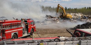 About seven fire fighters work Monday afternoon to cool the area by spraying water on piles of burning garbage at the Hay River dump. Photo by Sarah Ladik NNSL