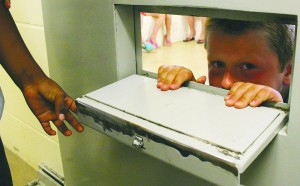 Bert Buckley checks out the inside of a holding cell with the rest of his Summer Heat group during a tour of the police detachment. Photo by Sarah Ladik NNSL