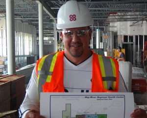 photo courtesy of Robert Hawkins Daryl Dolynny holds up the floor plan for the new hospital.