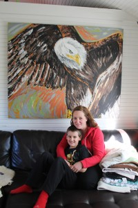 Sarah Ladik/NNSL photo Cash Rewega, left, and Natacha Kruger hang out in their home in Old Town where Natacha creates all her work, such as the painting of the eagle hanging in their living room.