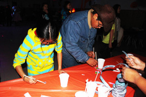 Sarah Ladik/NNSL photo Fiona Huang, left, and Ira Cayen participate in a game at this year's Spook-o-rama event involving picking up candy with chopsticks.