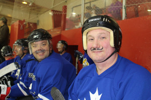 Cst. Yannick Gagnon (left) and fire fighter Joseph Robertson get into the Movember spirit for a fundraising game against all levels of minor hockey Oct. 30. Gagnon, the game's organizer, says the even raised over $600. Photo by Sarah Ladik NNSL