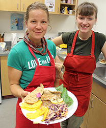 Franziska Ulbricht (left) and Marie Schmidt serve up fresh and tasty food at the Real Food Cafe at the season's first Winter Market organized by the Hay River Commons and hosted by Ecole Boreale. Photo by Sarah Ladik NNSL