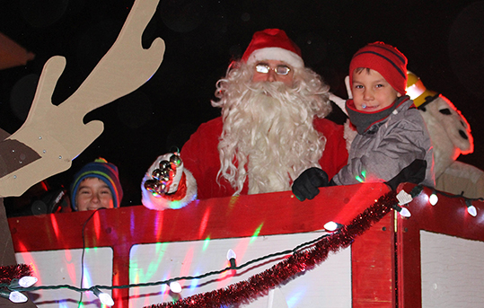 Conner McKay Ivanko, left, Santa Clause, and Everett Durocher man the town's float during the annual Santa Clause Parade last week. Sarah Ladik NNSL