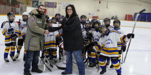 Sarah Ladik/NNSL photo Steve Campbell, left, hands Pennie Pokiak a check on behalf of the Hay River Elks Club who are proud to sponsor the Atoms hockey tournament.