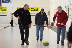 Jared Monkman/NNSL photo Danny Jackson, left, Jr. Barnes, and Ron Hogan follow a rock thrown down the ice at last week's Territorial Firefighters' Curling Championships.
