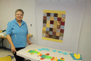 Sarah Ladik/NNSL photo Germaine Michel shows off her latest project in her home last week. Michel is back behind her desk at DJSS this week training her replacement, but looks forward to the day when she can devote more time to quilting.