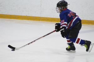 Sarah Ladik/NNSL photo Jack Pettipas takes the puck up the ice in the opening game agaisnt fellow-Hay River team in last weekend's novice tournament.