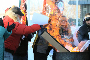 Sarah Ladik/NNSL photo Jack Bourassa, left, throws copies of an open letter Mayor Andrew Cassidy sent to municipal workers asking them to return to work and cross picket lines into the fire last Thursday.