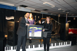 Photo courtesy of Wendy Morgan Mayor Andrew Cassidy, left, presents Alfred Mansell Citizen of the Year recipient Louise Schumann with a painting by a local young artist at this year's Chamber Gala.