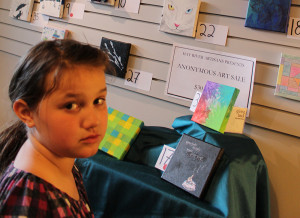 Sarah Ladik/NNSL photo Evelyn Beck stands back to admire the work done by various anonymous artists in Hay River in the first Anonymous Art show hosted at She Takes the Cake cafe. Beck was the youngest participant in the event.