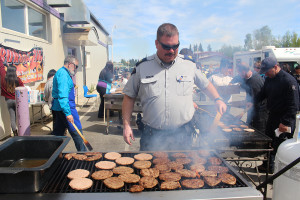 Staff Sergeant Chad Orr flips burgers in front of the Diamond Jenness Secondary School shop to feed the over 1,200 participants, their coaches, and champerones. In all, the organizers prepared more than 3,000 burgers over the course of the three-day event. Photo by Sarah Ladik NNSL