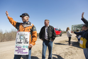 Jared Monkman/NNSL photo Jack Bourassa, left, and Todd Parsons stand with strikers along the highway. Strikers made a 'virtual' picket line next to the Pine Point bridge in protest of the meeting happening on the reserve. May 7, 2015 Hay River, Pine point bridge
