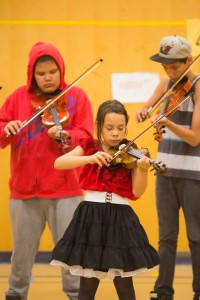 Jared Monkman/NNSL photo Bridgette McKay plays the fiddle at a performance at Chief Sunrise School on Friday afternoon.  Bridgette McKay plays the fiddle at a performance at Chief Sunrise School on Friday afternoon.  Behind her are Raymond Norn and Myles King-Villebrun.