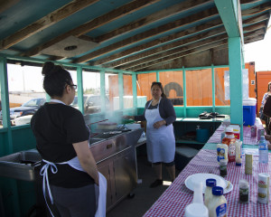 Jared Monkman/NNSL photo Sasha Cayen, left, and Shannon Buckley cook fish and fries at the first weekend of the wharf Saturday.
