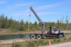 A truck waits on the site where the vehicle containing the remains of Brian Boucher was found, waiting to pull it out of the pond July 6.
