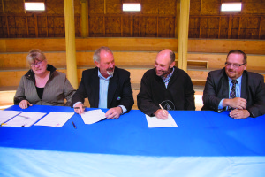 Jane Groenewagen, left, John Rodda, Andrew Cassidy, and Robert Bouchard take part in the signing Wednesday afternoon. June 10, 2015
