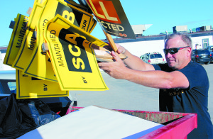 Kim Tybring Employee of the  Town of Hay River and strike captain of walkout from  Puts picket signs in the dumpster after the strike ended.