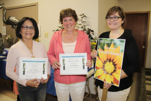 Two of the main winners in Hay River Yards in Bloom 2015 were People's Choice Award recipient Lilia Alexander, left, and the Darm Crook Award overall winner Karen Hordal, centre. They are joined at an annual awards ceremony on Aug. 15 by Lorie Steinwand, the co-ordinator of Hay River Yards in Bloom.