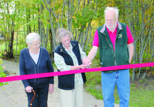 Paul Bickford/NNSL photo Three long-time volunteers with the Hay River Museum Society – left to right, Marge Osted, Vicky Latour and Peter Osted – cut a ribbon on Sept. 11 to officially open a new trail and park area in which exhibits are displayed at the Hay River Heritage Centre.