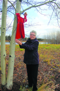 Eileen Hamilton poses after hanging a small red dress and doll in a tree along the Mackenzie Highway on Oct. 11 in memory of her murdered cousin Geraldine Settee.